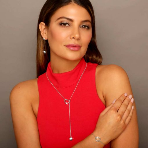 Millennial woman in red wears Twisted Heart & Orb lariet Necklace Rhodium over Sterling Silver with 2 clear diamond cut CZ stones Heart bracelet on her hand and orb earrings designed by ARY D'PO