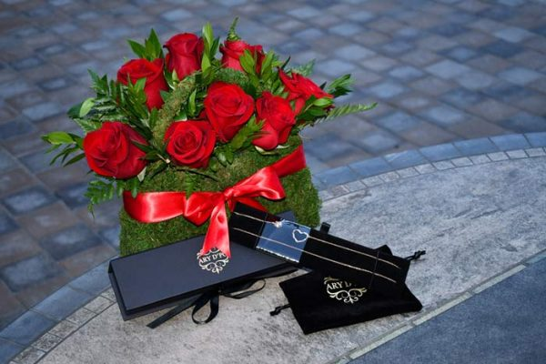 ARY DPO Hearts and Orbs necklace placed with the branded packaging and a beautiful bouquet of red roses