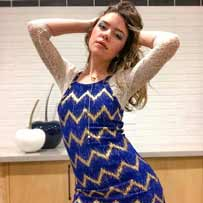 Testimonial Audrey Smith millennial woman in blue dress s beaded body both hands up to her head with lariat gold heart and orb necklace designed by ARY D'PO