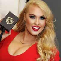 Darcy Donovan Actress, Writer, Producer, Singer, Entrepreneur wearing red dress and red lipstick holding black box with gold logo of ARY D'PO and elegant gold Twisted Swirl Necklace on her neck