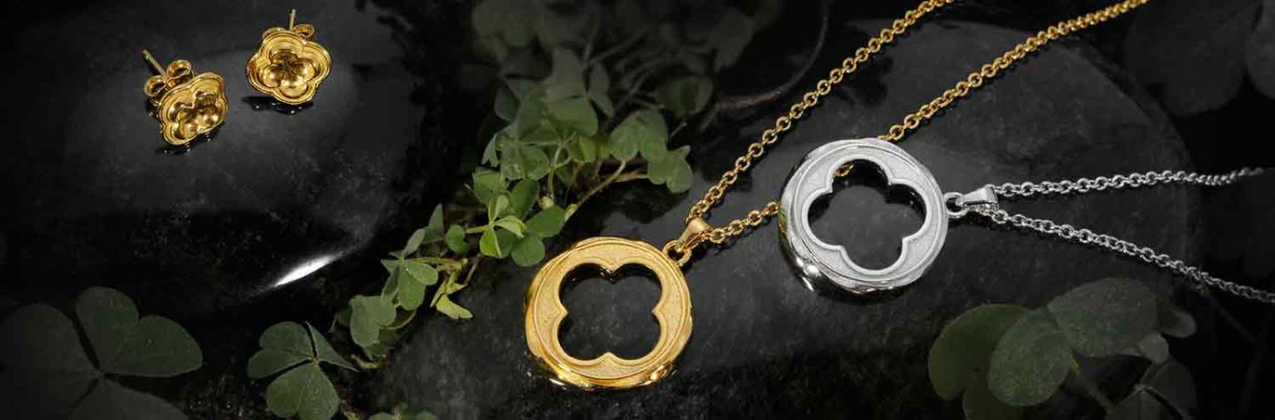 ARY D'PO Four Leaf Clover Jewelry Collection Quatrefoil ornament in gold and silver beautifully arranged on black wet stones surrounded by green clover plants.