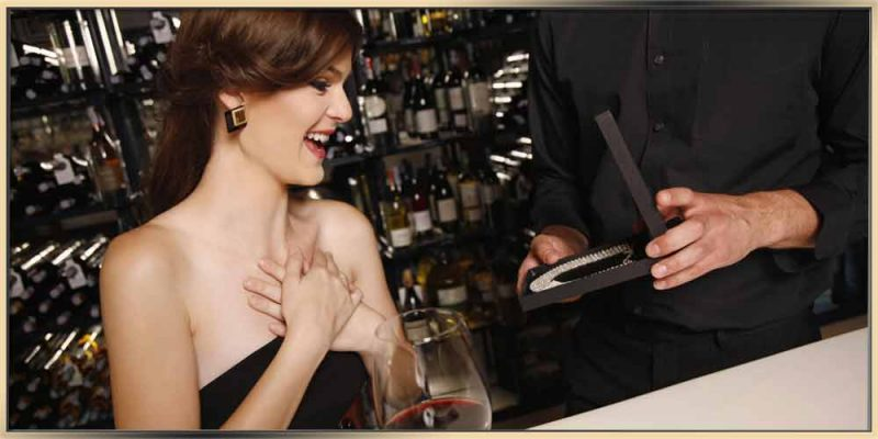 A beautiful young woman with brown hair up, wearing a black evening dress, is being surprised when she sees her jewelry gift. She's holding her hands together at her chest and smiling at the gorgeous necklace in the black jewelry box that is being presented to her. There is a glass of wine on the table in front of her as well. This picture is a great reflection of the ARY D'PO's article about jewelry as a gift.