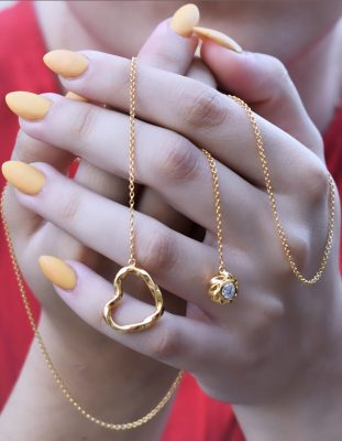Heart necklace as symbolic jewelry is presented by a young woman wearing red cloth holding in her hand the 18K Gold plated sterling silver Twisted Heart & Orb lariat necklace by ARY D'PO as a symbol of love.