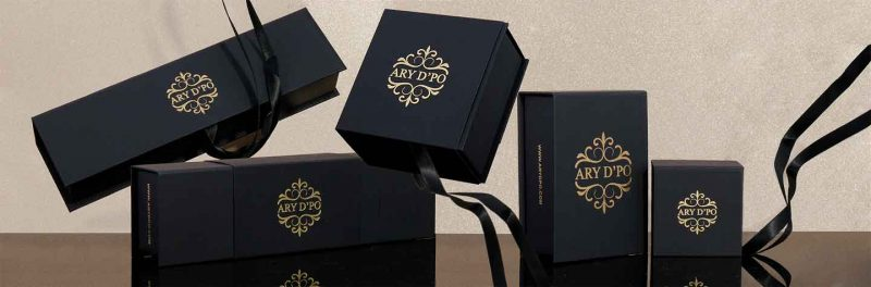 ARY D'PO Packaging and care. Various black boxes for jewelry with gold lead logos