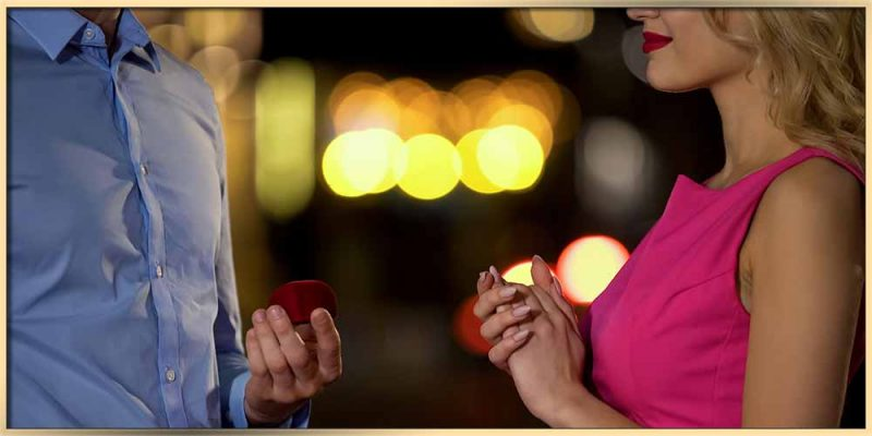 How expensive should a jewelry gift be? Evening, a man in blushirt with a box of jewelry standing in front on beautifule waman in red she is smiling and exited