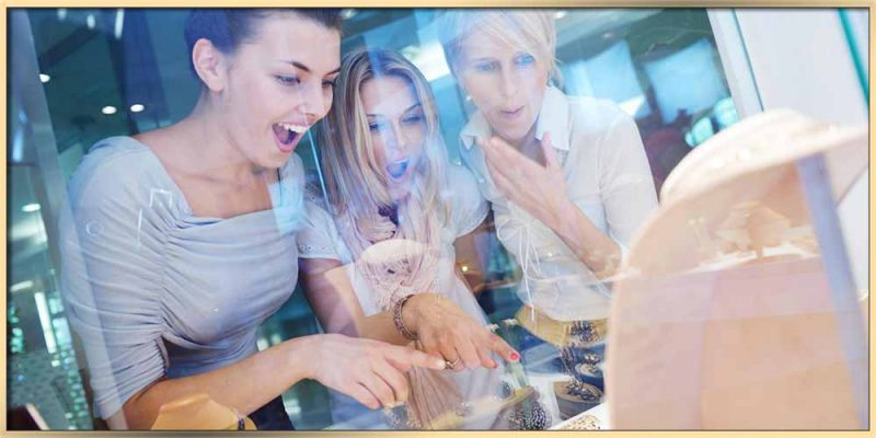 An image of three young women looking into the jewelry store through the window featured for Why Do Women Love Jewelry? article
