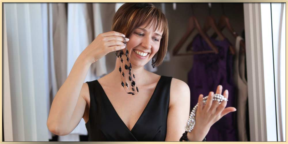 A woman wearing a black evening dress choose the perfect jewelry for an occasion