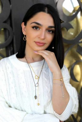 ary dpo Twisted Hearts and Orbs sterling silver collection in yellow gold and rhodium showcased by a young woman
