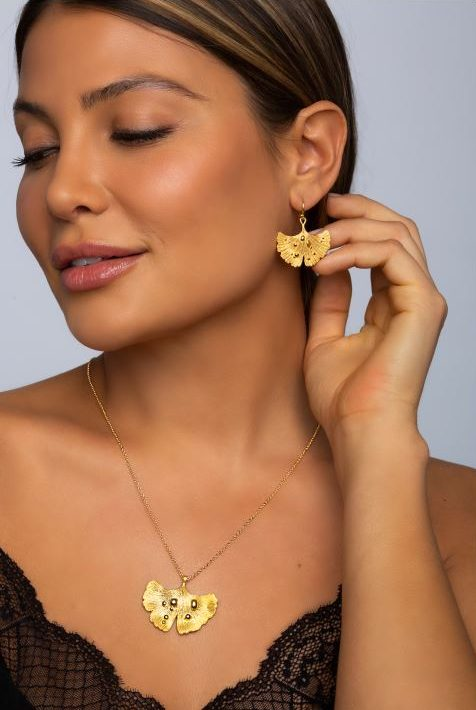 arydpo Ginkgo Leaf After Rain Jewelry Collection in gold presented by a beautiful model wearing a black top