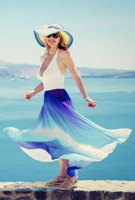 A model wearing a blue & white maxi dress and a hat with a sea in the background for Your Guide to Summer 2021 Fashion Trends