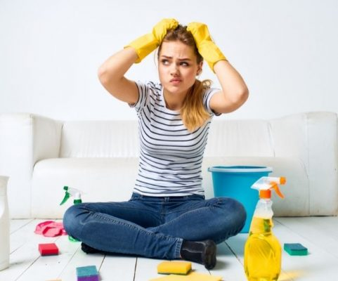 A woman is ready to clean the house sitting on the floor and holding her head while wearing yellow cleaning gloves. She looks concerned.