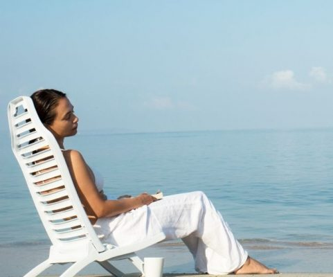 a woman wearing white beach clothing relaxing on a white chair on the beach