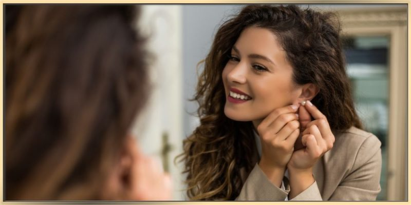 A beautiful woman with curly long dark hair is putting on earrings while looking into mirror and smiling