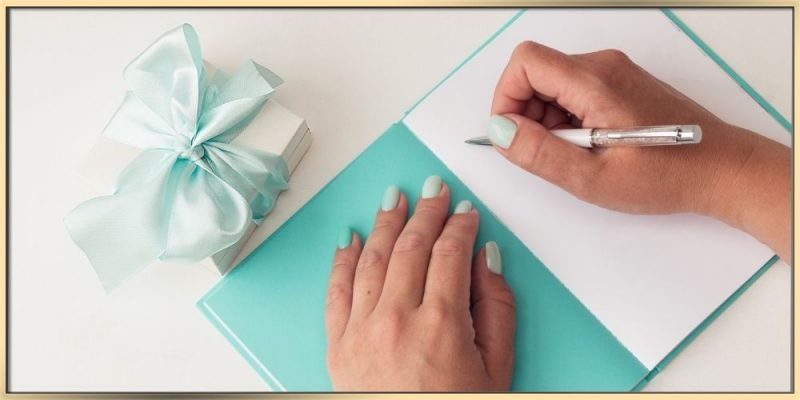 arydpo presents a white jewelry box with a Tiffany blue ribbon on a white surface and a greeting card of the same colors. There are two hands, one hand is on one side of the card and another one has a pen implying that the person is ready to write a gift message. The nails on the hands match the theme colors of white and Tiffany blue.