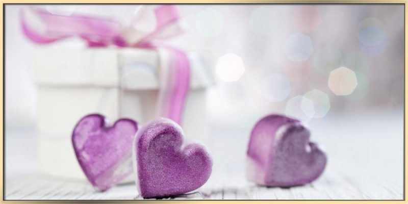A white gift box with purple ribbon and small heart-shaped ornaments in purple on a white background