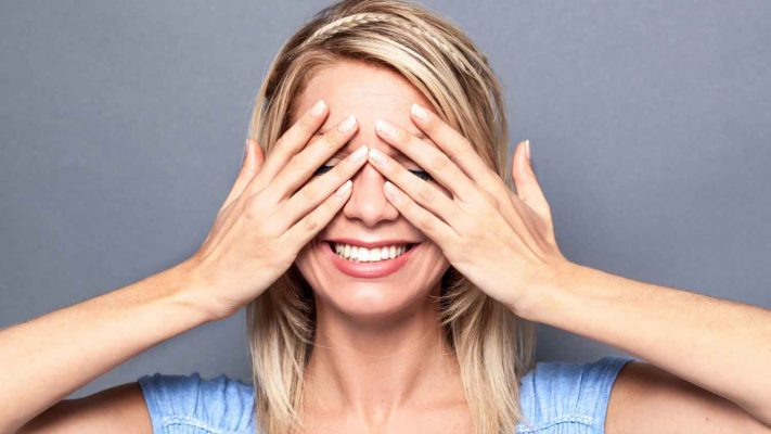 A young woman with blond hair wearing a light blue top is smiling while closing her eyes with her hands
