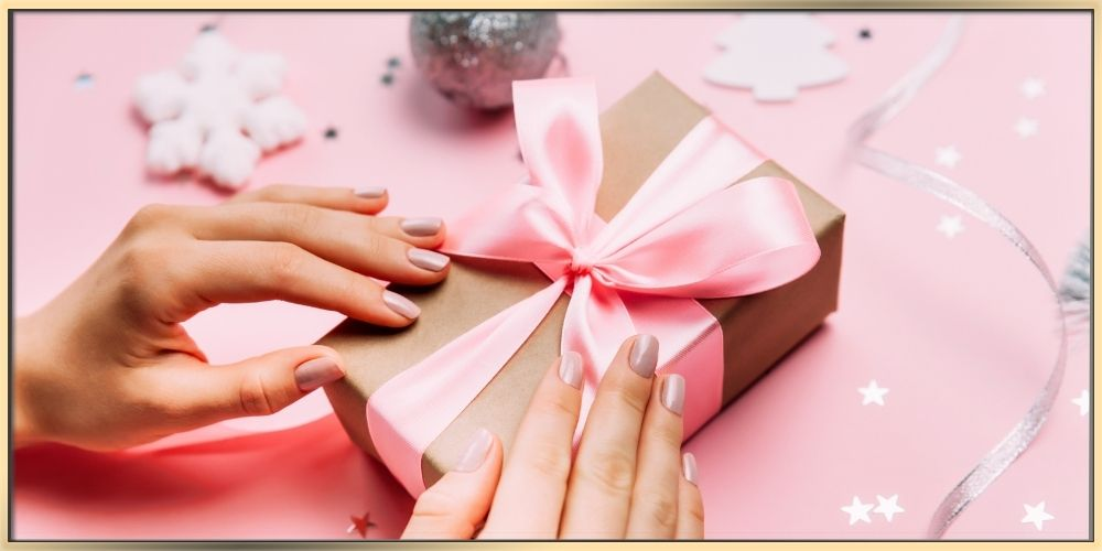 A woman's hands with clean beautifully done nails finishing wrapping a holiday gift while surrounded by a holiday ornaments.