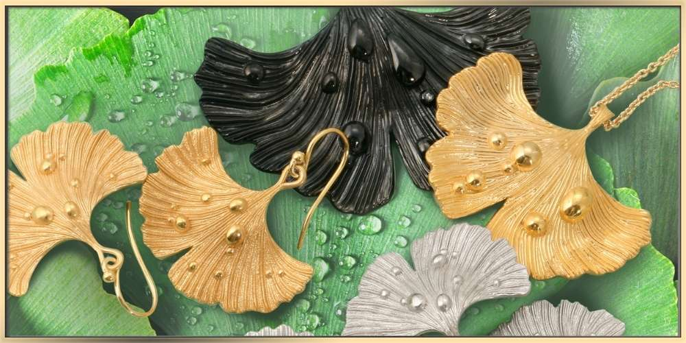 The ARY D'PO Ginkgo Leaf After Rain jewelry collection on the wet green leaves with droplets