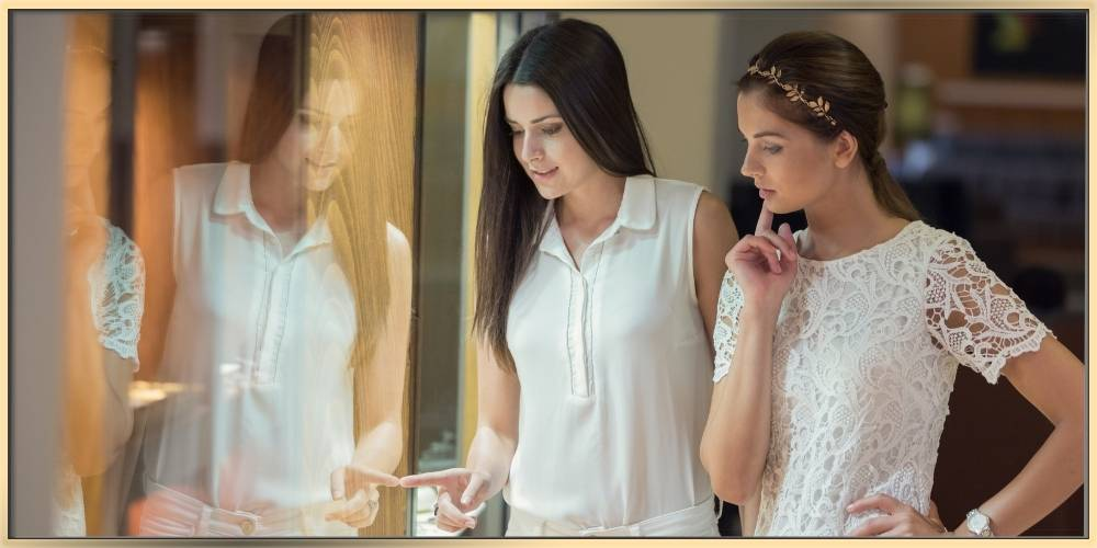 twos young women with long hair wearing white cloths are looking into the store through the window