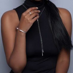 Urban Marquise Y Slider Necklace in silver with white Swarovski crystals on a model with dark skin and black long hair wearing black turtleneck sleeveless top
